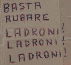 """Cartone con la scritta """"Basta rubare ladroni! Ladroni! Ladroni"""""""