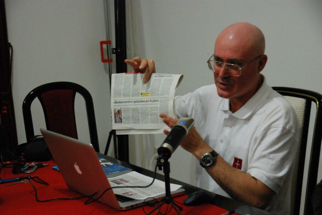 """Roberto Giurastante mostra alla platea una copia del giornale locale che riprende la dicitura """"eversivo e pericoloso per la pace"""" per descrivere il ricorso al TAR presentato da Trieste Libera."""