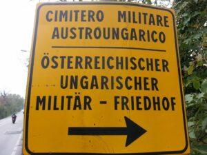 Cartello stradale bilingue italiano-tedesco che indica il Cimitero Militare Austroungarico di Prosecco-Prosek.